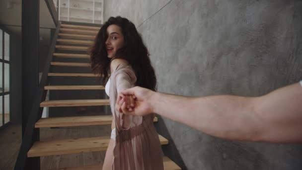 sexy Frau hält Mann Hand zu Hause. romantisches Mädchen flirtet mit Freund.