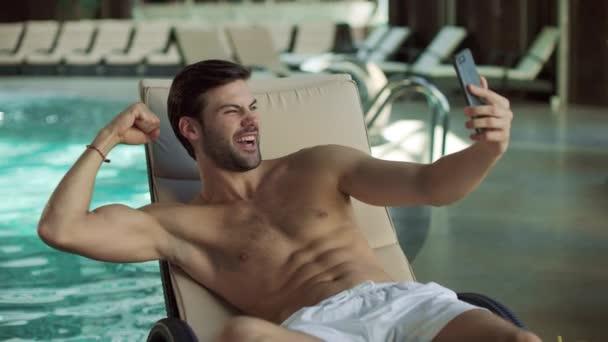 Nahaufnahme Mann Spaß in der Nähe Pool Indoor. Mann macht Selfie mit Handy