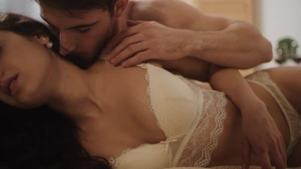 Nahaufnahme sinnliches Paar, das sich in Zeitlupe im Bett umarmt. sexy Liebhaber küssen.