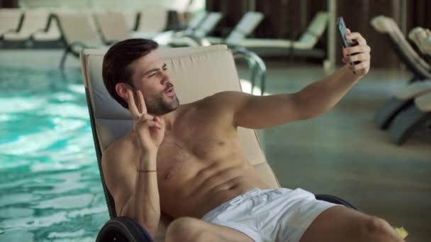 schöner Mann macht Selbstporträt auf Handy am Pool