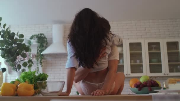 Man hands hugging women hips in slow motion. Woman buttocks sitting on table