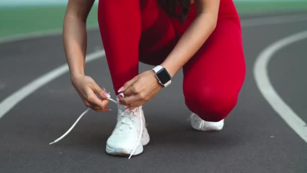 Close up of fitness woman lacing up footwear for marathon on track