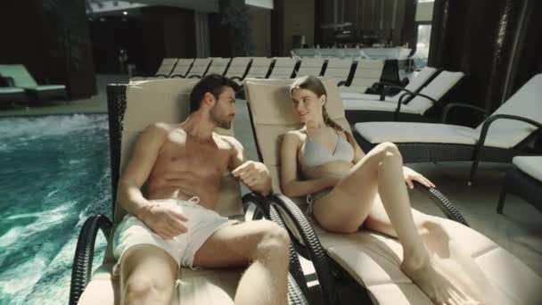 Closeup young couple lying on loungers poolside. Man and woman relaxing at spa