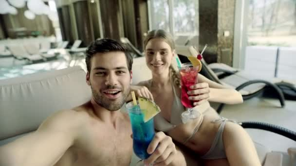 glückliches Paar macht Selfie mit Cocktails. Lächelnde Familie am Pool