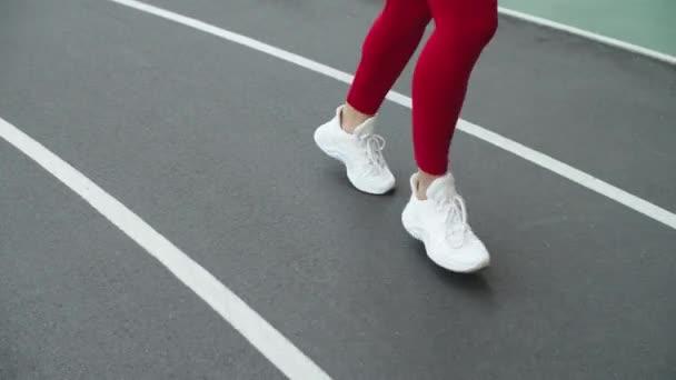 Detailní záběr běžkyň běžících na sportovním stadionu. Samičí nohy běží