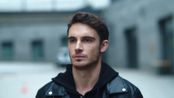 Szekrény fiatal férfi néz kamera a városi háttérben. Egy jóképű férfi portréja.