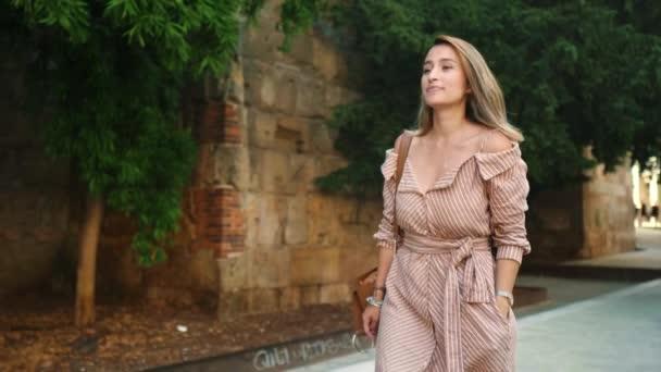 Touristin, die an der alten Stadtstraße spaziert. Gebräuntes Mädchen sucht Sightseeing