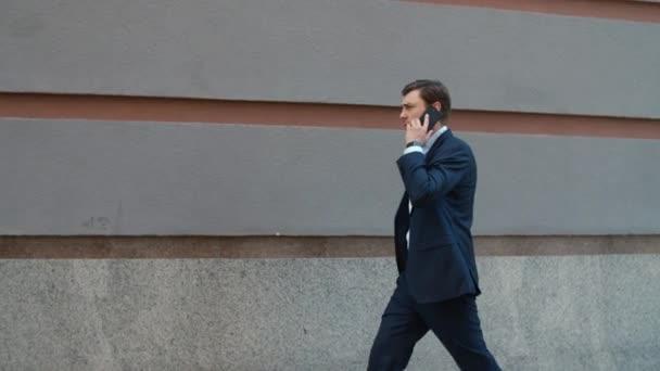 Obchodník z bočního pohledu, telefonuje na ulici. Muž kráčí do kanceláře
