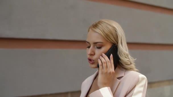 Porträt einer telefonierenden Frau im Freien. Frau telefoniert über Geschäfte