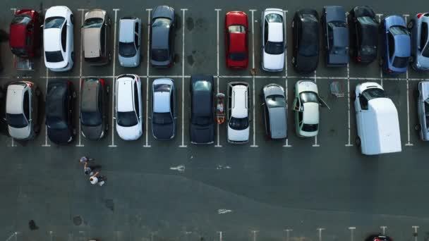 Drone footage man opening car door. Copter flying above supermarket parking