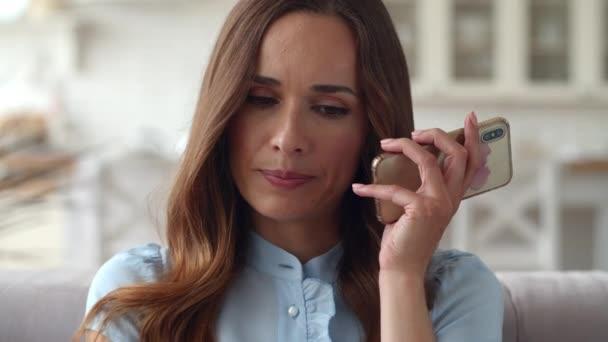 Szomorú nő telefonál az otthoni irodában. Zaklatott lány beszél telefonon.