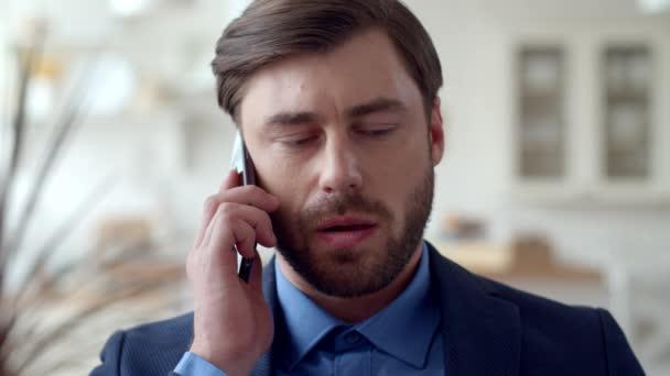 Vážný obchodník mluví po telefonu v domácí kanceláři. Chlápek mluvící telefon.