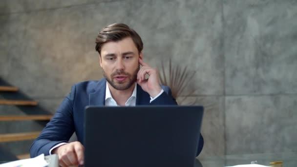 Vážný obchodník, který dělá webovou konferenci na notebooku. Chlap mluvící na webové kameře