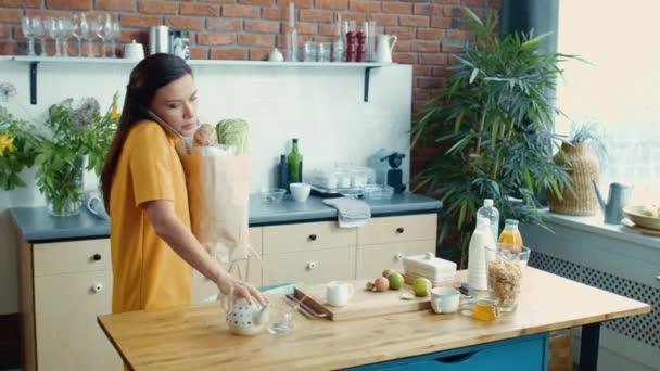 Žena přinášející domů nákupní tašky. Usmívající se dívka mluví po telefonu v kuchyni.