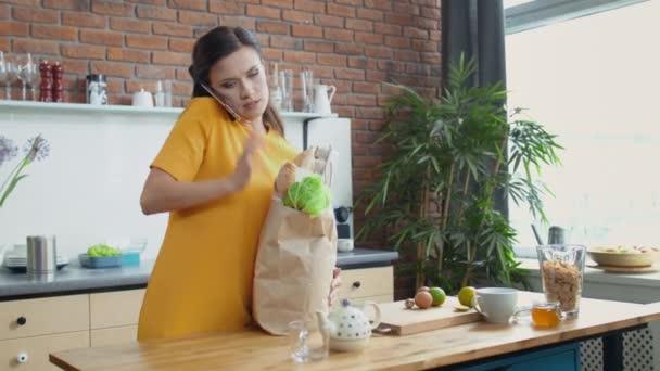 Žena nosí tašky v kuchyni. Bruneta končí telefonát doma.