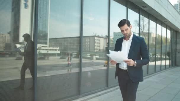 Blízký obchodník chodící s papíry na ulici. Podnikatel čte dokumenty