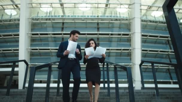 Geschäftspaar geht mit Dokumenten spazieren. Paar diskutiert Geschäftspapiere