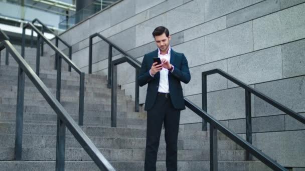 Obchodník používá telefon na schodech venku. Podnikatel se usmívá na schodech