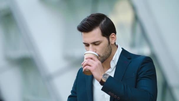 Portrétní muž s kávou a telefonem. Muž pije odnést kávu