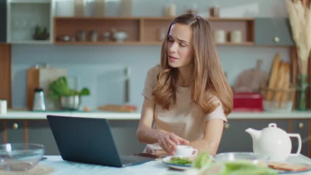 busnesswoman working on laptop at remote workplace.Woman drinking coffee at home