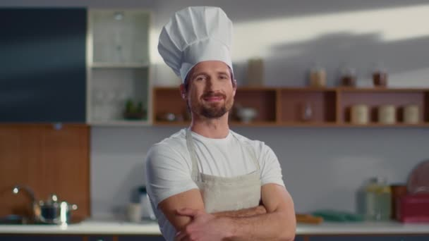 Portrait of chef standing at workplace. Man crossing hands on kitchen