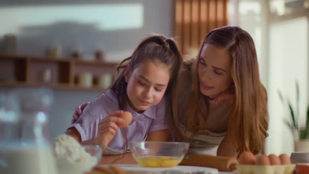 Smiling mother and daughter cracking egg into mixing bowl on kitchen