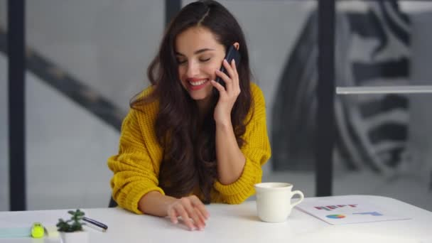 Closeup smiling businesswoman talking mobile phone in office