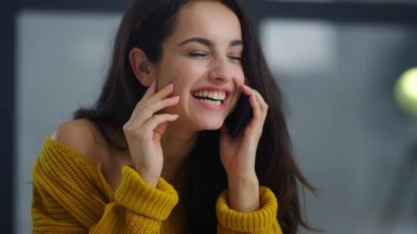 Fröhliches Mädchen lacht Handy am Arbeitsplatz. Entspannte Geschäftsfrau lächelt
