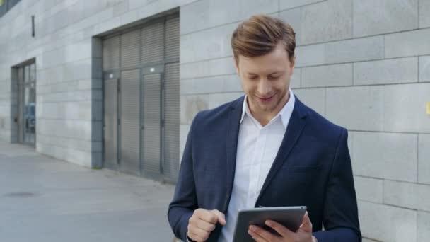 Obchodník používající digitální tablet na ulici. Dělník slaví vítězství venku