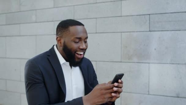 Africký obchodník čte dobré zprávy po telefonu. Zaměstnanec slaví vítězství