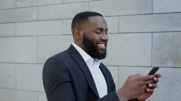 Usmívající se obchodník používající smartphone na ulici. Byznys muž procházky ve městě