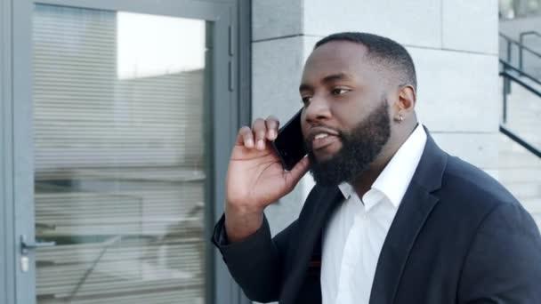 Afro obchodník argumentuje na smartphonu ve městě. Mužský manažer mluví po telefonu
