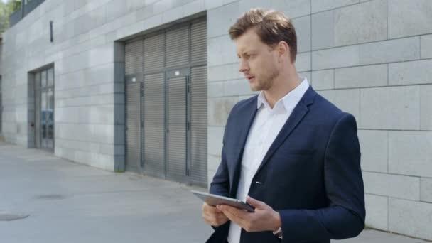 Podnikatel pracuje na tabletu na ulici. Správce čeká na partnera na ulici
