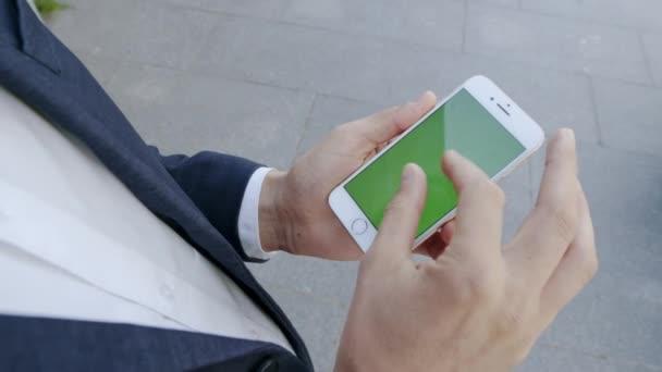 Obchodník používá mobilní telefon na City Street. Manažer pracující na telefonu venku