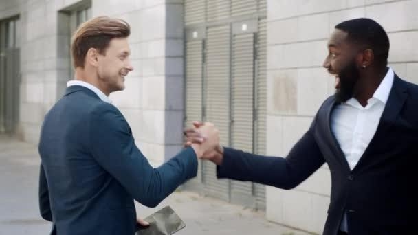 Businessmen receiving good news on tablet at street. Business partners hugging