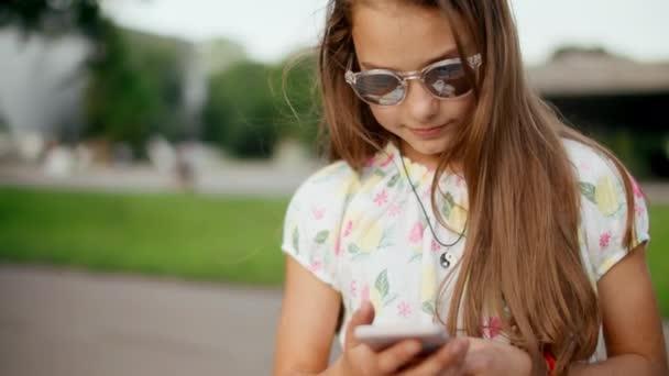 Mosolygós tini lány szörfözés internet mobiltelefon a nyári parkban.