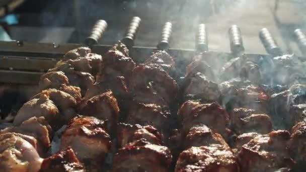 Shish kebab vaří venku. Grilování brambor se šunkou a sýrem