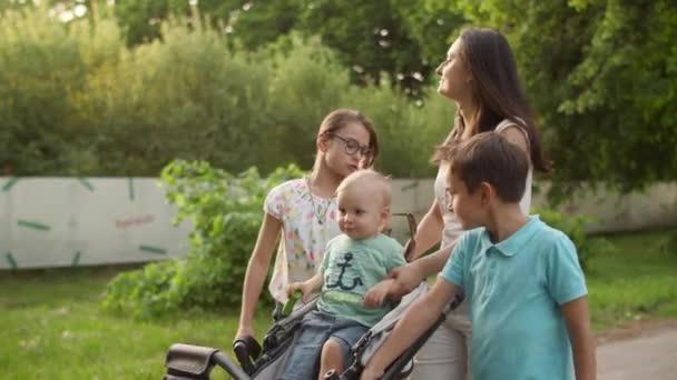 Uvolněná matka chodí se třemi dětmi. Šťastný rodinný odpočinek v letním parku