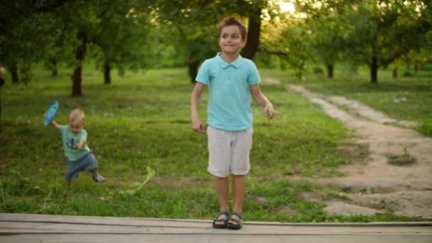 Usmívající se teenager tancující venku. Menší kluk nesoucí talíř frisbee ven