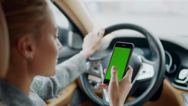 Porträt einer Frau mit Greenscreen-Handy im Auto. Frau mit Smartphone