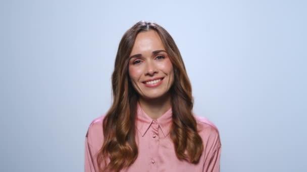 Obchodní žena se usmívá na kameru na modrém pozadí. Dáma pózuje před kamerou