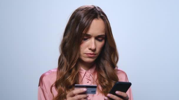 Geschäftsfrau kauft online auf Smartphone im Studio ein. Frau mit Kreditkarte