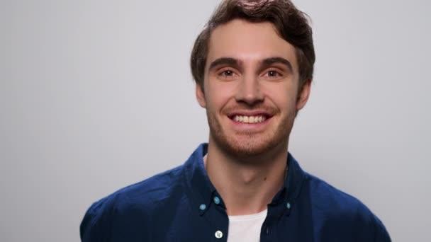 Muž se usmívá na kameru na bílém pozadí. Pozitivní chlap stojící ve studiu
