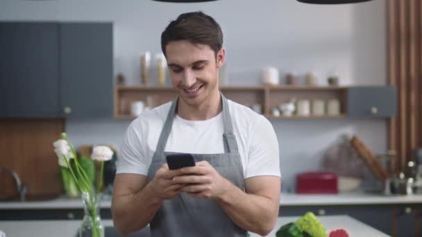 Man Koch suchen Rezept auf dem Handy in der heimischen Küche. Chef plant neues Gericht