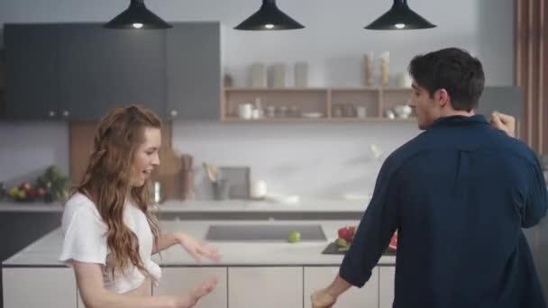 Fröhliches Paar tanzt zusammen in der Küche Hintergrund. Aufgeregte Freunde bewegen Körper