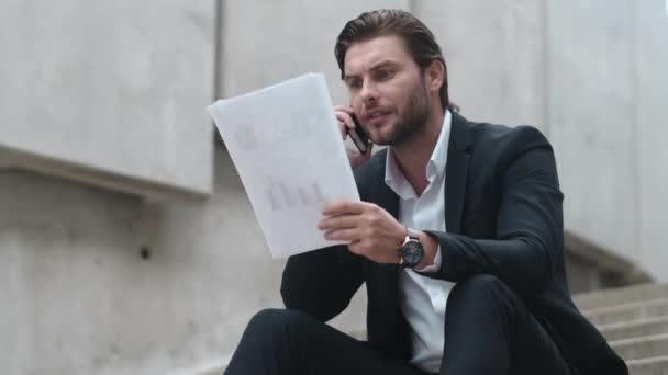 Obchodník mluví přes smartphone na ulici. Podnikatel slaví úspěch