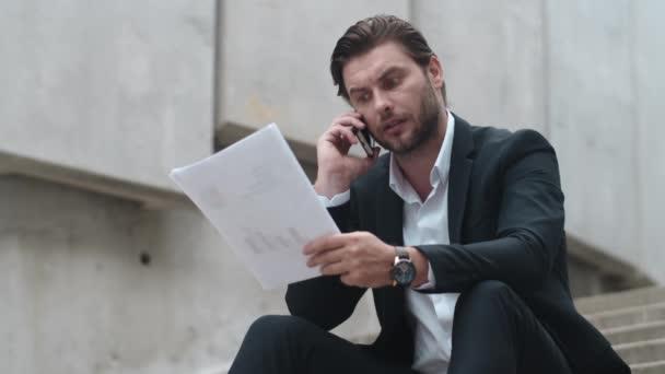 Obchodník mluví na smartphone s klientem.Muž pracuje s dokumenty venku