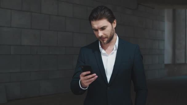 Obchodník používá smartphone na ulici. Manažer textové zprávy na mobilním telefonu ve městě