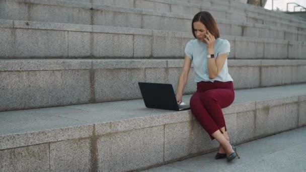 Geschäftsfrau spricht draußen auf dem Smartphone. Frau arbeitet am Laptop