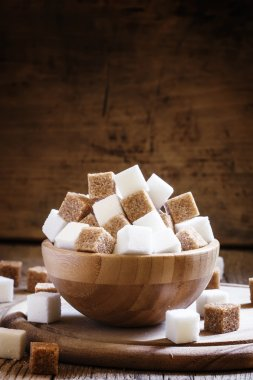 Refined sugar cubes, vintage wooden background